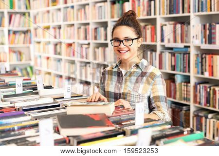 Schoolgirl in the library. Library, teenager  chooses a book. Student in the school library.