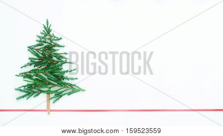 Christmas tree made from pine leaves, cinnamon, red seed on white background and red ribbon line, copy space