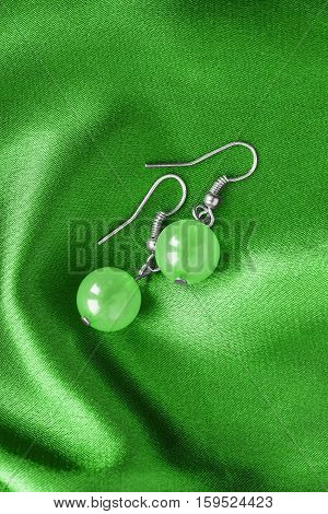 Nephrite earrings on green satin as a background