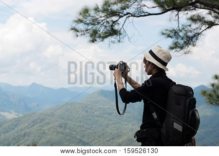 Asian woman traveler take photo on the hill
