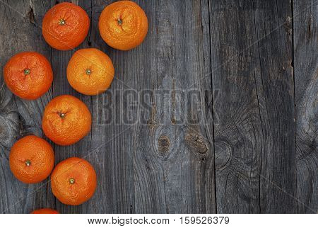 Ripe orange mandarins on the gray wooden background top view an empty space on the right