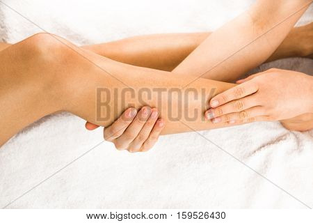 Beautiful legs of young woman with hands of masseur on white towel