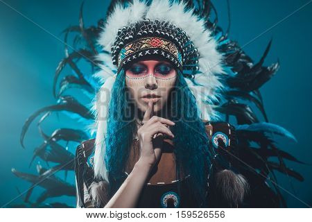 Native American woman isolated on blue wall