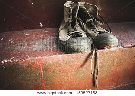 Old Sneakers Stand On Red Concrete