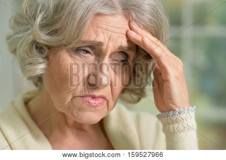Portrait of uppset senior woman with hand on her forehead