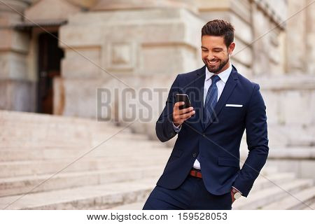 A handsome young businessman smiling and standing on the stairs while using his phone