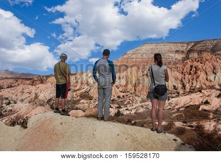 A group of tourists walk between the colored rocks in Cappadocia, Turkey