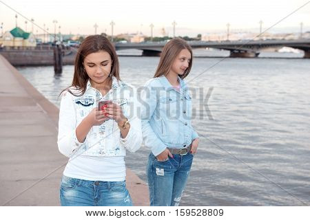 Two young beautiful girls are walking through the city