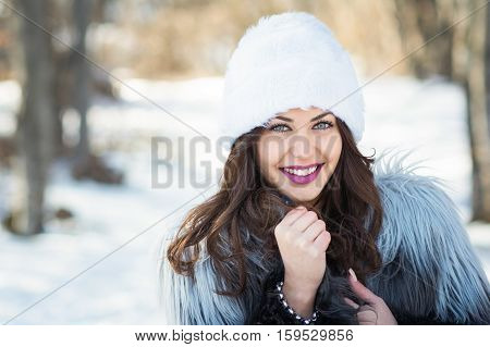 Gorgeous young woman winter portrait. Closeup portrait of beautiful young woman in fur hat and fur coat outdoors on snowy day in park. Natural light, retouched, closeup.