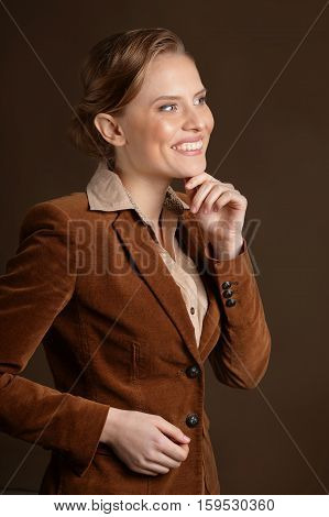 Portrait of happy young woman looking at distance against grey background
