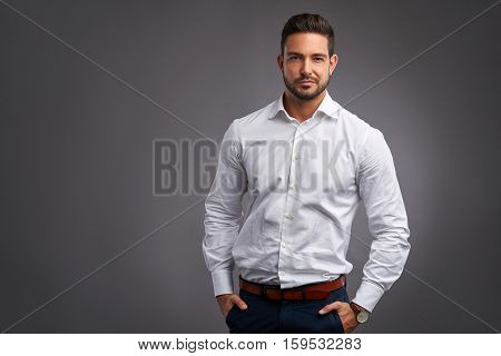 A handsome confident young man standing and smiling in a white shirt.