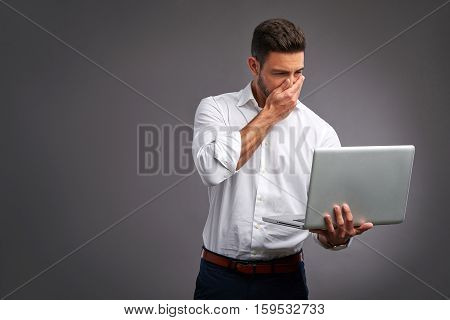 A handsome young man feeling confused while looking at a laptop in a white shirt