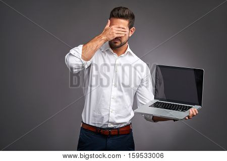 A handsome young man feeling stressed and grabbing his head while showing the screen of a laptop
