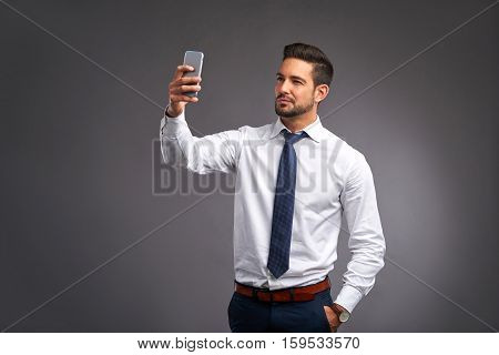 A handsome young man taking a selfie with his phone