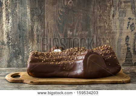 Chocolate yule log christmas cake on wooden background