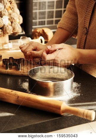 woman prepares dough for gingerbread house in the kitchen next is a sieve with flour and rolling pin