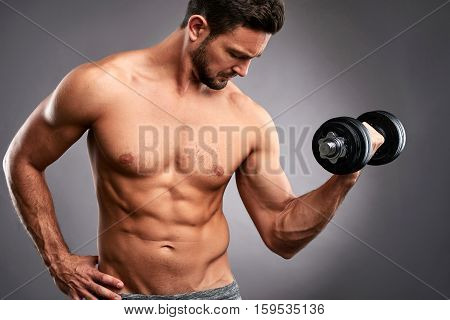 Close up picture of a half naked handsome young sportsman lifting a dumbbell with one hand