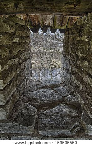 Stone arrowslit in the strengthened fortress wall. In the territory of the fortress Porkhov (The Pskov Oblast, Russia).