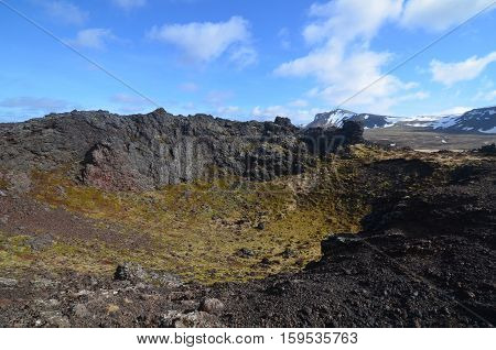 Blue skies and clouds above a volcanic crater in Iceland.