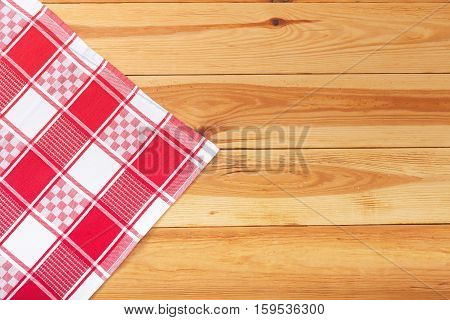 Wooden table covered with tablecloth. Empty tablecloth for product montage. Free space for your text. Top view.