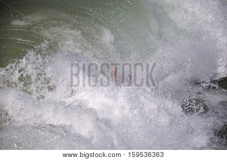 A surfer wiping out in the waves crashing against manhattan beach california on the west coast.