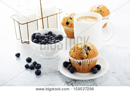Bright and airy breakfast with blueberry muffin, big cup of coffee and milk in bottles