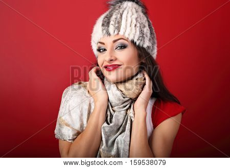 Happy Smiling Makeup Woman In White Fur Winter Hat And Fashion Scarf On Red Background With Red Lips
