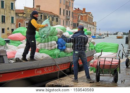 Venice, Italy - November 23, 2015: two men are unloading sacks from the boat in Venice, Italy