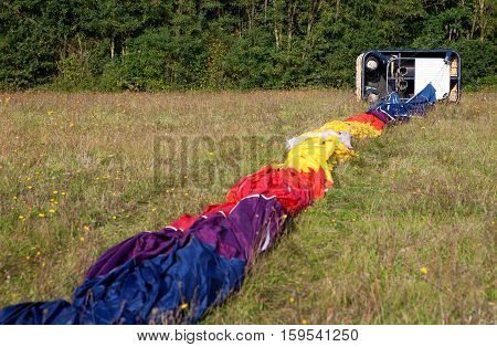 Wicker Gondola And Hot Air Balloon Envelope On The Ground, Ready For The Inflating
