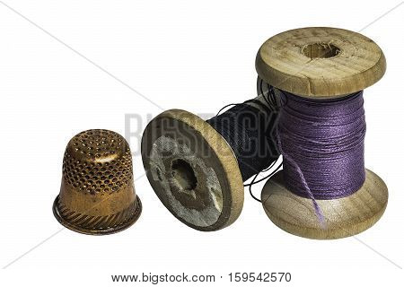 Two sewing spools with thread and thimble on white background