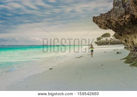 ZANZIBAR, TANZANIYA- JULY 17: tourist girl jogging on beautiful african beach with rockson on July 17, 2016 in Zanzibar
