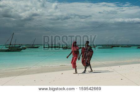 ZANZIBAR, TANZANIYA- JULY 13: Masai walking on Zanzibar coast with wooden boats on the background on July 13, 2016 in Zanzibar