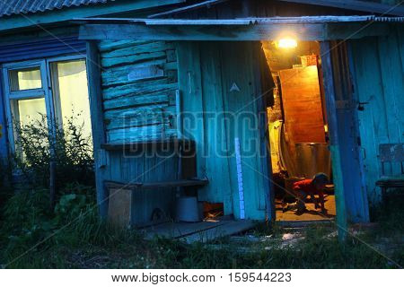 Opened Door In Night In Terrible House With Warm Light Inside. Horror Background In Night. Warm Insi