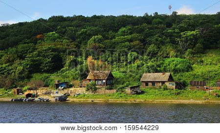 Fishing Village On Bank Of River In Green Forest. Old Wooden Houses On Edge Of River Stay On Hill. C