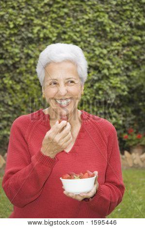 Senior Lady Eating Strawberry
