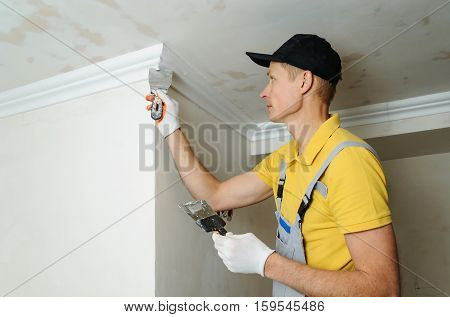 Installation of ceiling moldings. Worker puts glue on plastic molding for fixing it to the ceiling.