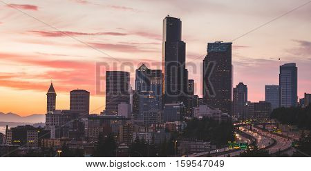 Sunset view of downtown Seattle. Skyscrapers on the skyline and long exposure streaks of light from traffic headlights.