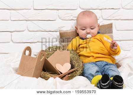 small baby boy with adorable curious face in yellow sweater and dummy leaned on pillow near straw wreath on white brick wall background