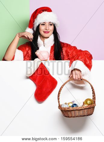 pretty cute sexy santa girl or smiling woman in red sweater and new year hat holds decorative christmas or xmas bucket with colorful balls and stocking or boot on purple green studio background