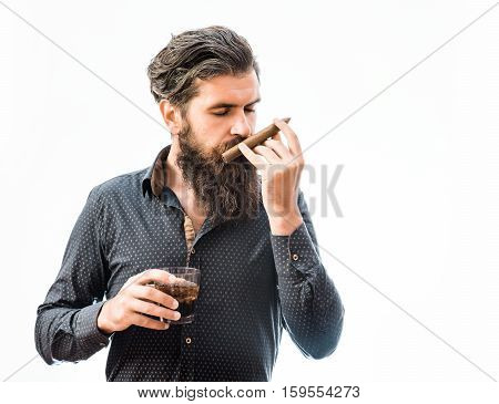 handsome bearded tough man with stylish hair mustache and long beard on serious face in blue fashion shirt sniff cigar and holding glass of whiskey isolated on white copy space
