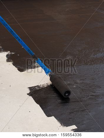 Roller brush. Worker covered surface bitumen primer for improving adhesion during surfacing rolled waterproofing during the installation of isolation on industrial or household objects. A waterproofing.