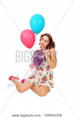 A beautiful young woman kneeling on the floor holding two balloons and a lollypop isolated for white background.