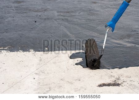 Roofer worker painting black coal tar or bitumen at concrete surface by the roller brush A waterproofing.