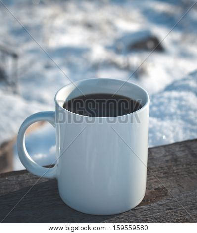 one cup of hot coffee in the winter on a snow-covered wooden table in nature