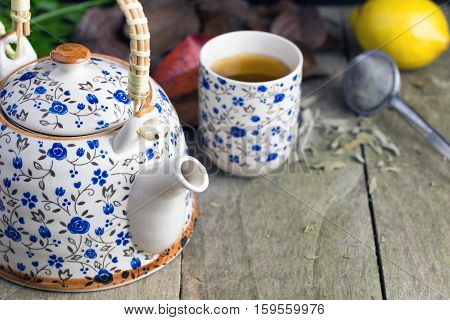 Autumn cup of tea with teapot on a rustic table.