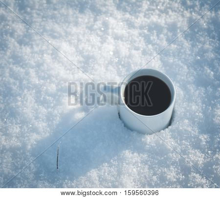 one cup of coffee in the snow