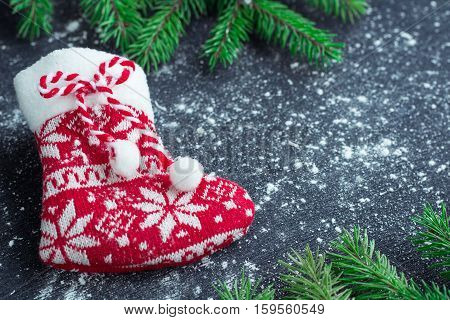 Christmas Red Stocking On Snowbound Black Background With Fir Branches