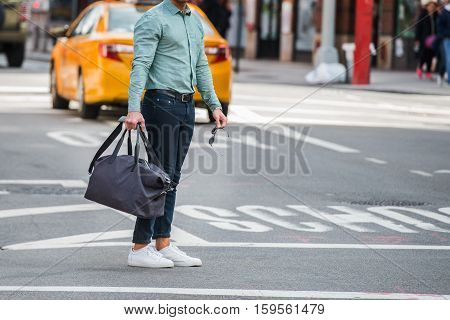 Elegant man walking on city street crosswalk wearing casual clothes with jeans ant t-shite and holding travel bag and sunglasses in hands