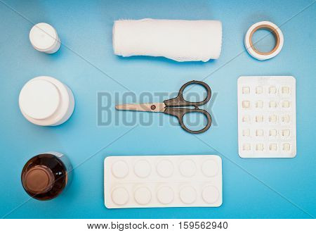 medical kit: scissors, bandages, pills on a blue background