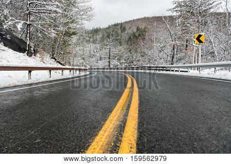 beautiful winter landscape with highway road with turn and snow-covered trees. Clean mountain aspahlt winter road with yellow marking double lines and singn.